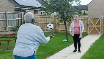 Two women, one wearing a mask, playing catch in the garden